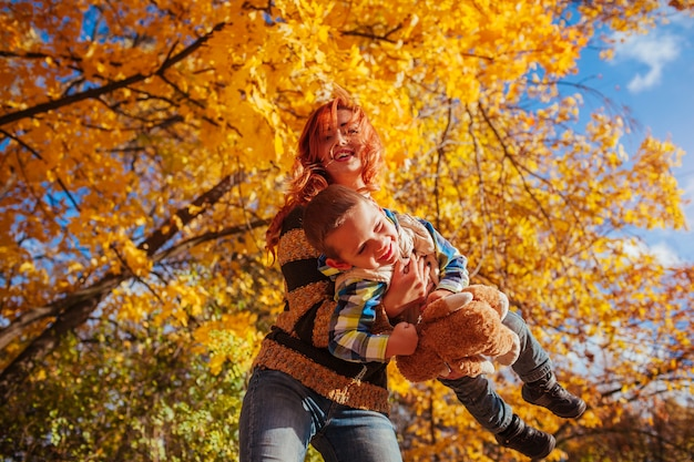 Madre felice e suo figlio piccolo che camminano e si divertono nella foresta di autunno.