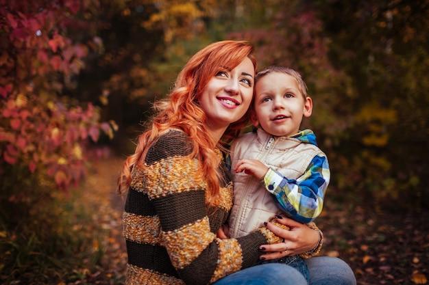 Madre felice e suo figlio piccolo divertirsi nella foresta d'autunno abbracciare mamma e bambino