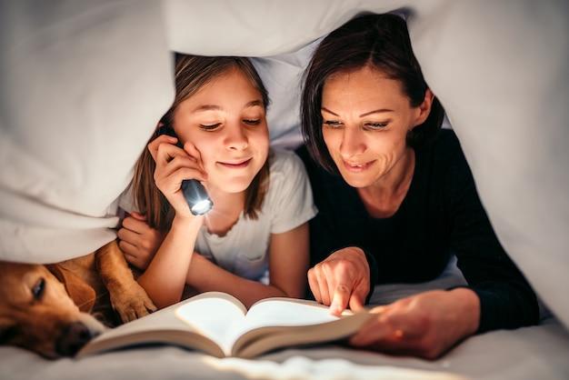 Madre, figlia e cane posa sul letto e libro di lettura a tarda notte