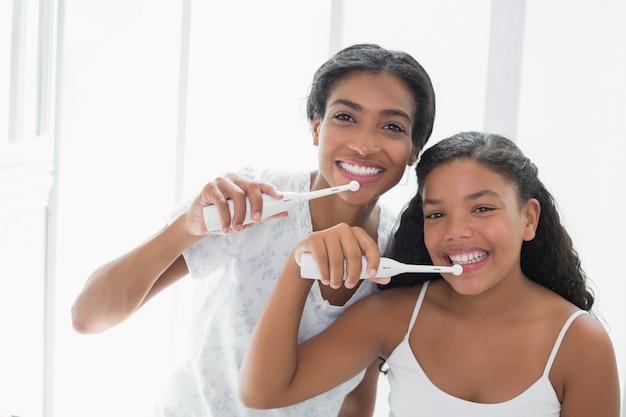Madre graziosa che si lava i denti con sua figlia