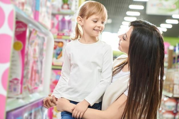 Madre in posa con il bambino nel negozio di giocattoli.