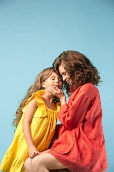 Madre incinta con figlia adolescente. ritratto in studio di famiglia