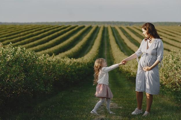 Madre incinta con sua figlia in un campo