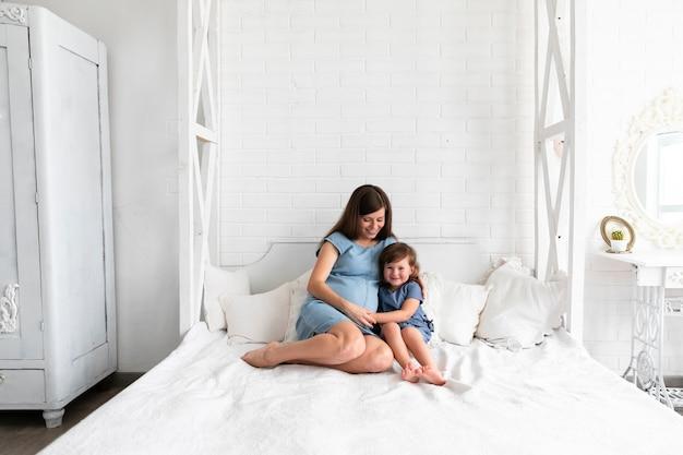 Madre incinta e figlia che soggiornano nella camera da letto