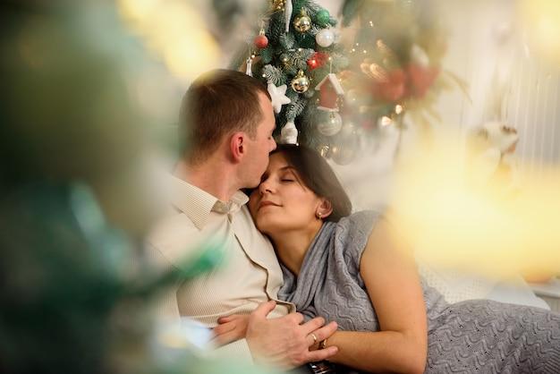 Madre incinta e suo marito a casa con decorazioni natalizie