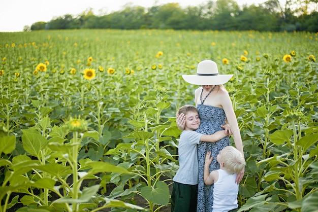 Madre incinta felice che abbraccia due piccoli figli