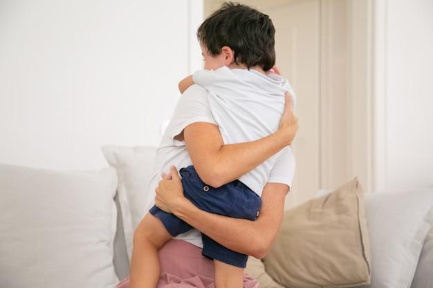 Madre irriconoscibile che abbraccia o abbraccia il figlio adorabile con amore.