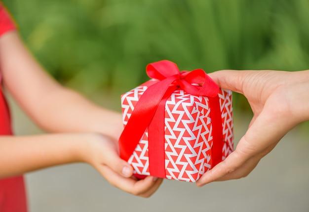 Madre mano dando una scatola regalo al suo bambino. vacanze, presente, concetto di natale