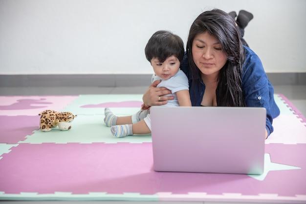 Madre messicana che lavora da casa posa al piano e giocando con il figlio