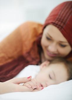 Madre musulmana araba che gioca e si prende cura del suo bambino