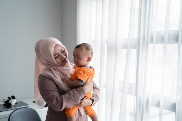 Madre musulmana asiatica che trasporta il suo ragazzino quando gioca vicino alla finestra