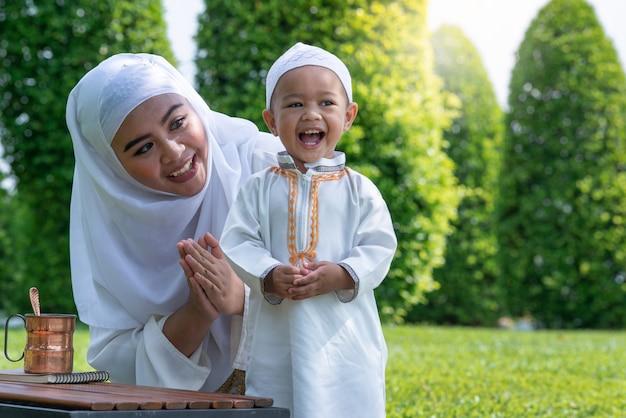 Madre musulmana asiatica e suo figlio che godono del tempo di qualità al parco, concetto musulmano della mamma e del figlio