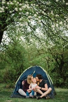 Madre, padre bacia e abbraccia un bambino godendo una vacanza in campeggio in campagna