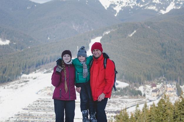 Madre, padre e figlio sono in piedi e sorridenti