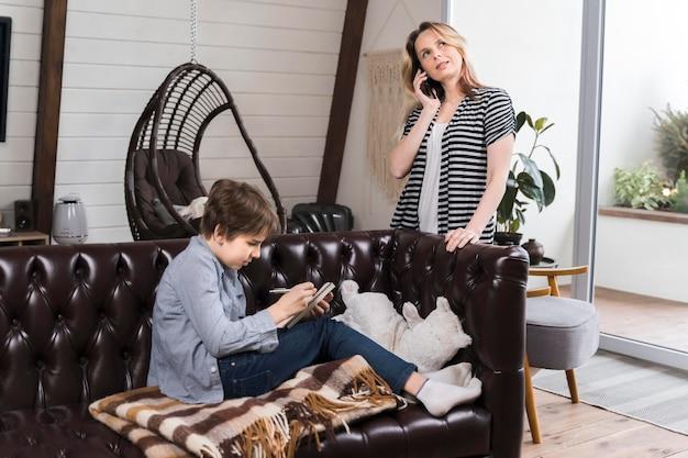 Madre parla al telefono mentre il figlio sta facendo i compiti