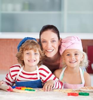 Madre radiosa che cuoce con i suoi bambini