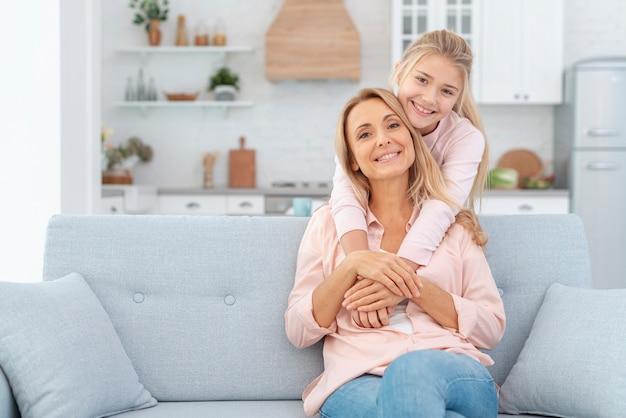 Madre seduta sul divano e abbracciata dalla figlia