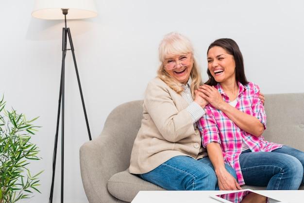 Madre senior allegra e sua figlia che si siedono sul sofà con la compressa digitale sulla tavola bianca