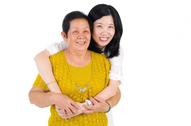 Madre senior della famiglia asiatica felice e prole adulta divertendosi tempo allo studio dell'interno.