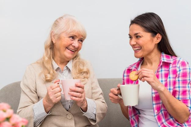 Madre senior sorridente e sua figlia che mangiano prima colazione insieme