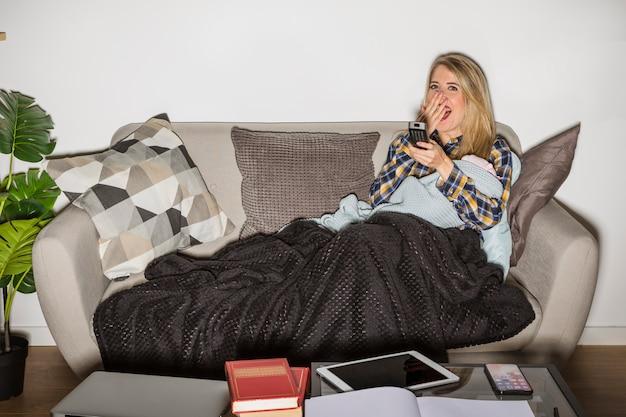 Madre sonnolenta con il bambino che guarda tv