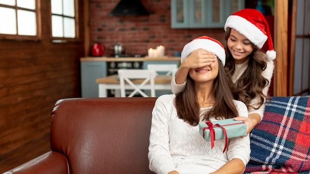 Madre sorpresa della ragazza del tiro medio con il regalo