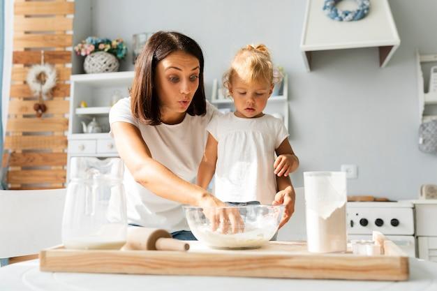 Madre sorpresa e figlia piccola che cucinano insieme