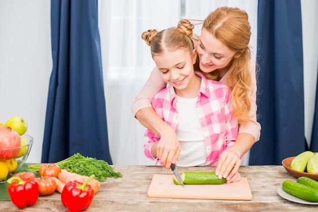 Madre sorridente che aiuta sua figlia a tagliare il cetriolo sul tagliere
