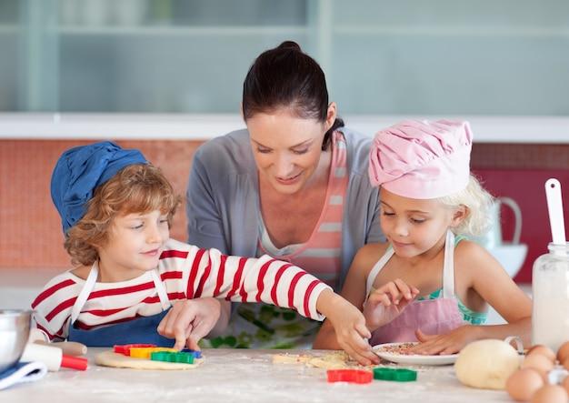 Madre sorridente che cuoce con i suoi bambini