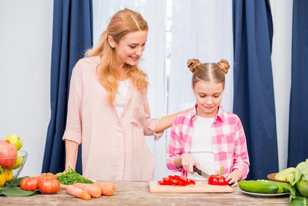 Madre sorridente che esamina sua figlia che taglia il peperone dolce con il coltello sul tavolo