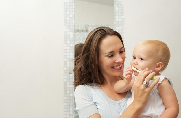 Madre sorridente che insegna al bambino sveglio come spazzolare i denti con lo spazzolino da denti