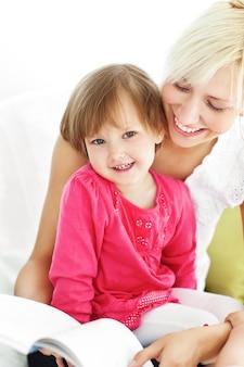 Madre sorridente che legge un libro con i bambini