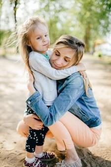 Madre sorridente felice che abbraccia la sua piccola figlia adorabile all'aperto. famiglia lifestyle.