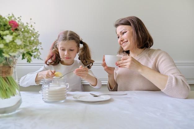 Madre sorridente felice e piccola figlia che bevono alla tavola delle tazze