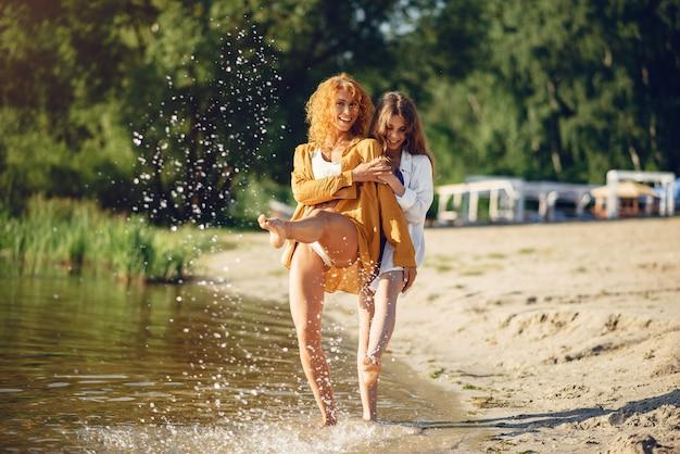 Madre sportiva con la figlia sveglia che cammina vicino al lago