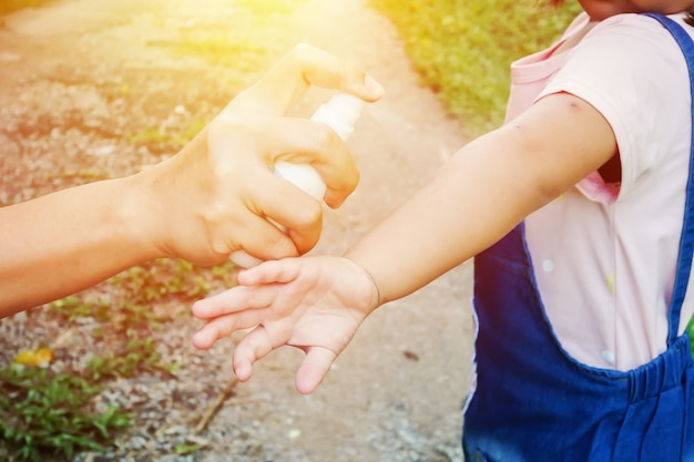 Madre spruzzando insetti o zanzare repellenti sulla pelle ragazza, zanzara repellente per i bambini