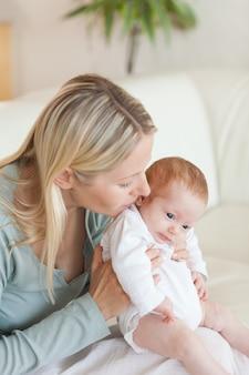 Madre sul divano che tiene il suo bambino