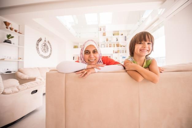 Madre tradizionale musulmana con il piccolo figlio sveglio a casa in salotto