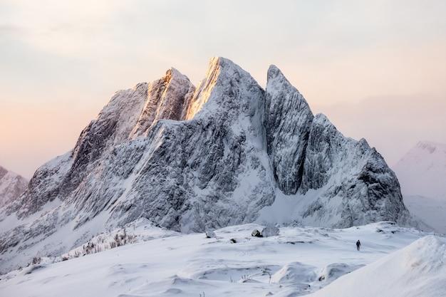 Maestosa montagna innevata con alpinista sulla collina di neve al sorgere del sole