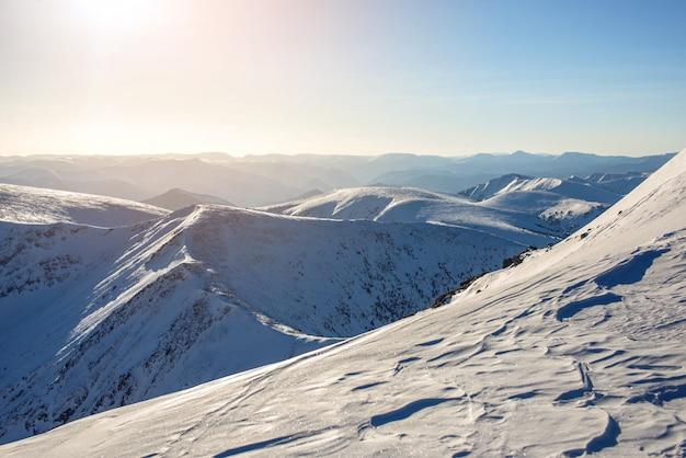 Maestoso paesaggio invernale di montagne innevate con cielo blu chiaro