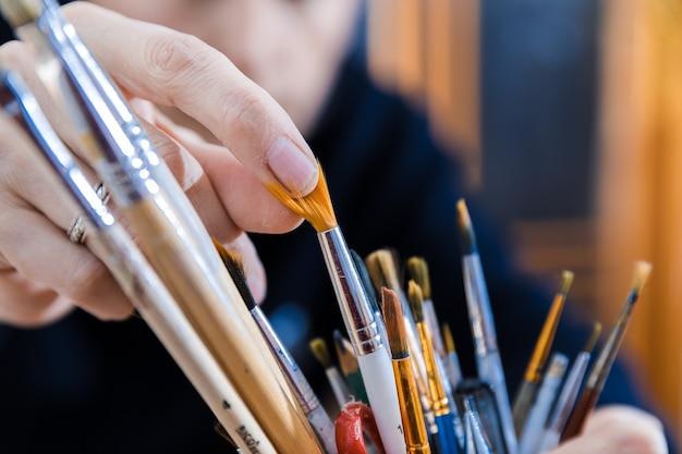Maestro che sceglie il pennello da pittura dal magazzino.