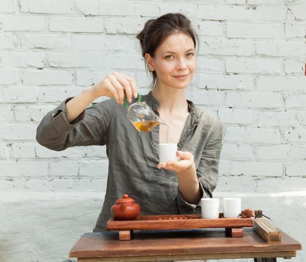 Maestro orientale della cerimonia del tè con muro di mattoni bianchi sullo sfondo.