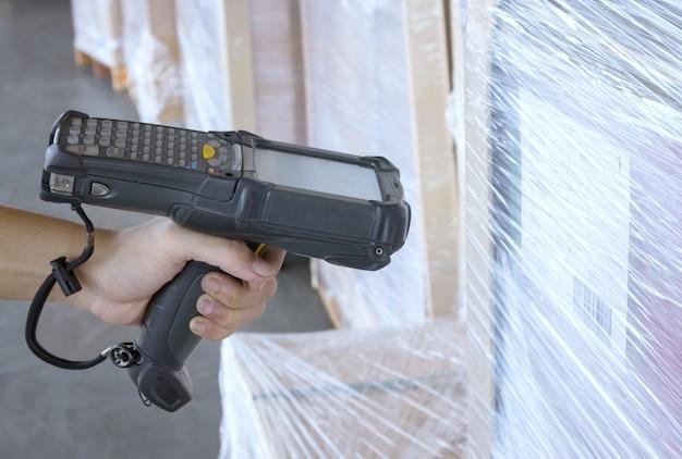 Magazziniere con scanner di codici a barre con scansione su pallet di prodotti.