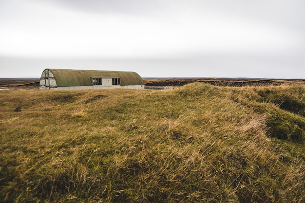 Magazzino abbandonato in un terreno incolto vicino a un prato.
