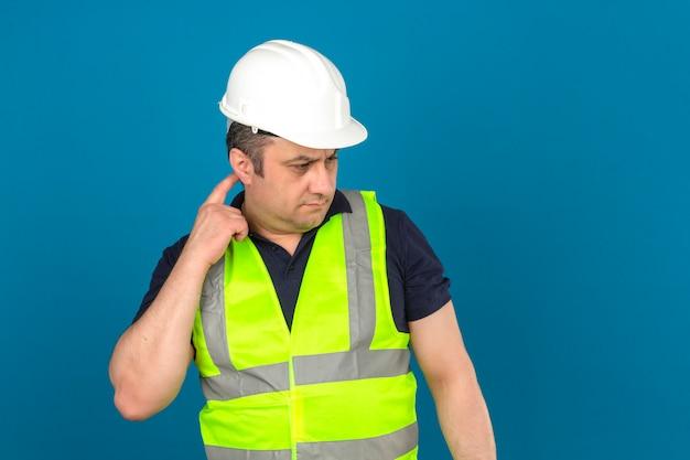 Maglia d'uso della costruzione gialla e casco di sicurezza d'uso dell'uomo invecchiato centrale che stanno con la testa commovente di sembrare pensieroso e che pensa sopra la parete blu isolata