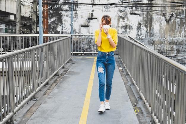 Maglietta asiatica della donna gialla che indossa la maschera di protezione respiratoria n95 contro inquinamento atmosferico che cammina a bangkok