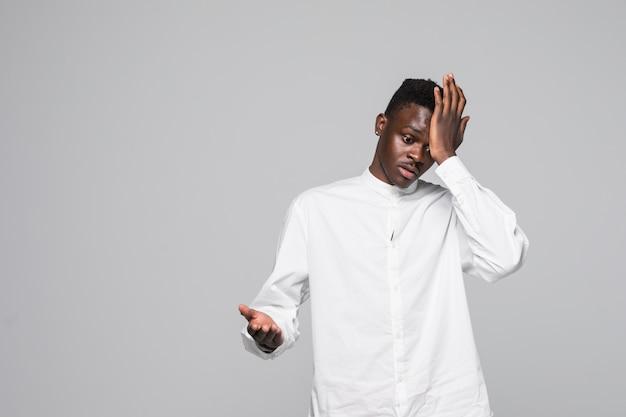 Maglietta bianca da portare del giovane uomo dell'afroamericano sorpresa con la mano sulla testa per l'errore, ricordi l'errore. dimenticato, cattivo concetto di memoria.