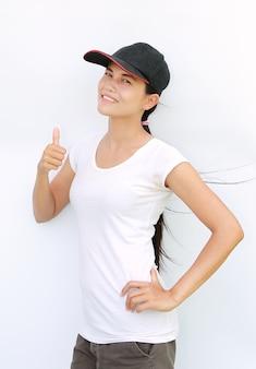 Maglietta e protezione asiatiche di usura di donna che mostrano pollice in su su priorità bassa bianca