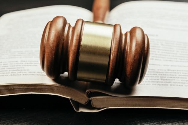 Maglio di legno marrone del giudice sul del libro aperto