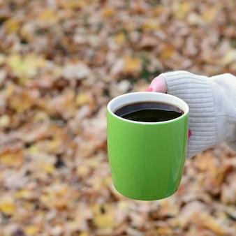 Maglione bianco da portare della donna che tiene una tazza di caffè verde